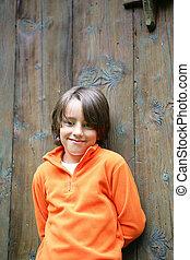 Boy stood by big wooden door