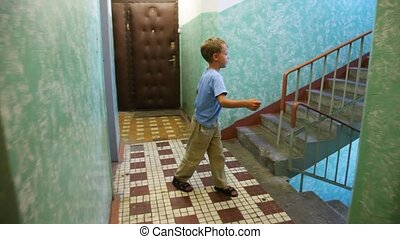 boy stop in tracks on stair platform in apartment house. Moving camera