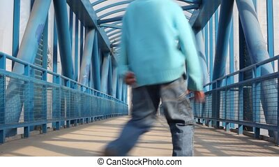 Boy strides on bridge