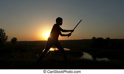 Boy Strikes Kung-Fu Blows With a Stick on a Lake Bank at Sunset