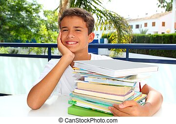 boy student teenager happy thinking with books stacked outdoors