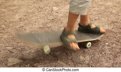 boy studies to go for a drive on a skateboard - little boy...