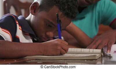 Boy Studying Education With Father Helping Son Doing School Homework