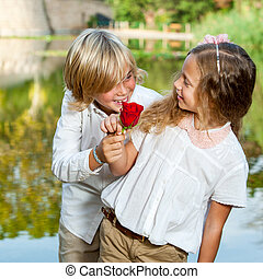 Boy surprising girl with flower.