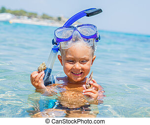 Boy swimming in sea - Portrait of young boy with seashells...