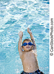 Boy swimming on his back in pool - Happy boy wearing swim...