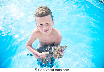 Boy swims in the pool with a dog