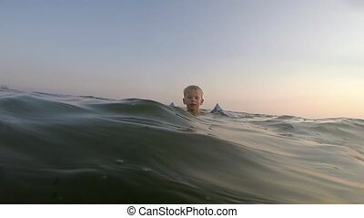 Boy swims in the sea