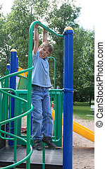 Boy swinging from a bar in a park