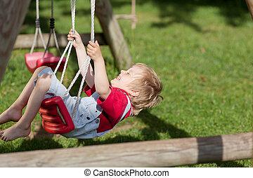 Boy Swinging In Playground - Cheerful little boy swinging in...