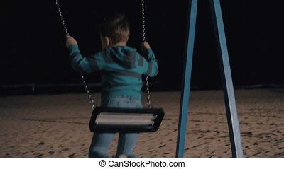 Boy swinging in the evening and looking at dark sea