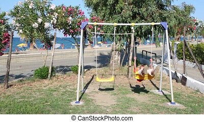 Boy swinging on a swing against the backdrop of the beach