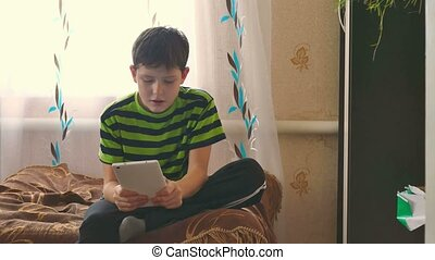 boy tablet playing game browsing internet sitting on the...