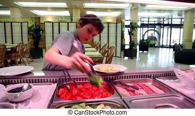 Boy takes food and put it on plate in restaurant - Boy takes...