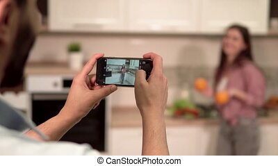 Boy Takes Picture of Girlfriend - Black-haired boy taking...