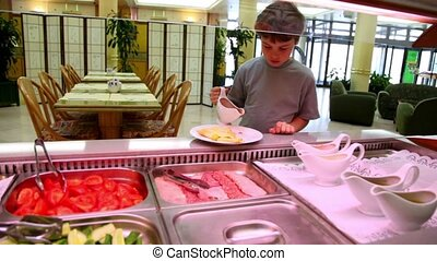 Boy takes pours sauce on plate and tastes it in restaurant -...