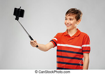 childhood, fashion and people concept - portrait of happy smiling boy in red polo t-shirt taking picture with smartphone on selfie stick over grey background