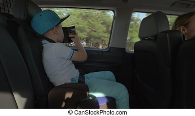 Boy taking pictures with cell when traveling by car