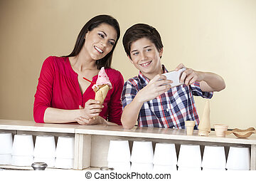 Boy Taking Self Portrait With Mother Holding Strawberry Ice...