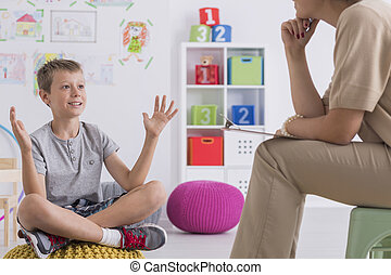 Boy talking with psychotherapist - Boy sitting on pouf in...
