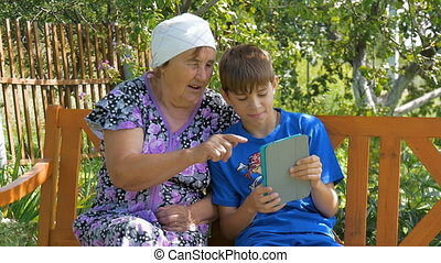 Boy teaches her grandmother how to use the tablet.