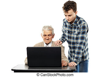 Boy teaching grandfather how to use a laptop