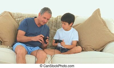 Boy teaching to his grandfather how to use a joystick in the...