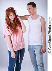 Teenage boy teasing her female colleague, vertical
