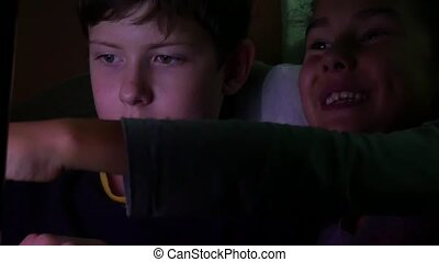boy teen and girl plays on the laptop at night online computer games