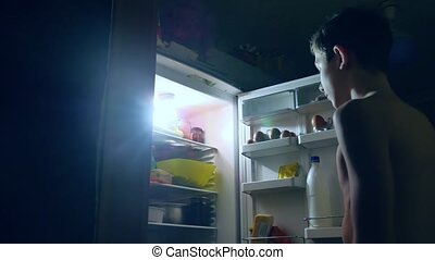boy teen diet gluttony eats at night from fridge. boy opens the refrigerator and indoors fridge