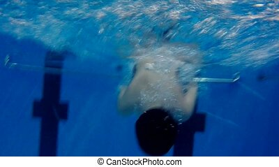 boy teen dives into underwater swimming pool