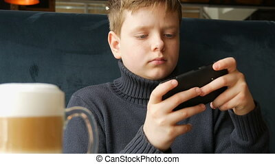 Boy teen playing a game on black smartphone