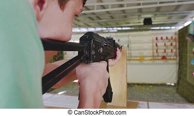 Boy teen shoots in a dash from the machine gun. Airguns -...