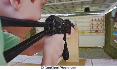 Boy teen shoots in a dash from the machine gun. Airguns gun....