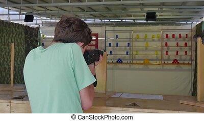 Boy teen shoots in a dash from the machine gun. Airguns gun...