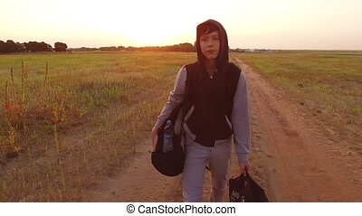 Boy teen traveling. Boy teenage tramp walking along the road...