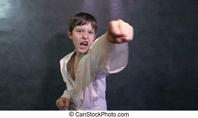 boy teenage in kimono karate fight hands waving fists slow motion