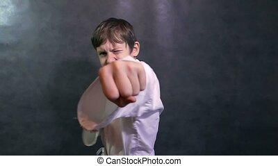 boy teenage karate in kimono fight hands waving fists slow motion