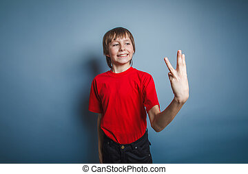 boy teenager European appearance in a red shirt showing...