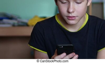 Boy teenager holds smartphone phone web online game the site