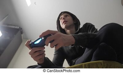 boy teenager in the hood playing video games lifestyle on...