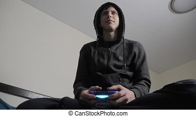 boy teenager in the hood playing video games on the console...