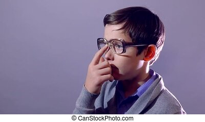boy teenager nerd portrait schoolboy corrects touches glasses on purple background education