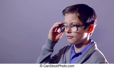 boy teenager nerd portrait schoolboy tired rubs his forehead perspiring glasses