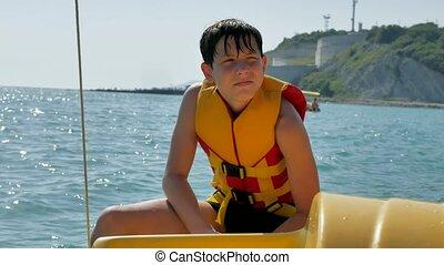 boy teenager on a yacht. sailor bathe in the open ocean...