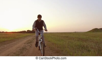 boy teenager riding a bike on a road in nature. boy teenager...