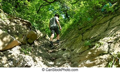 Boy teenager rises to the mountains along the trail. A...