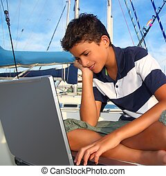 boy teenager seat on boat marina laptop computer summer...