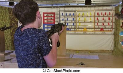 Boy teenager shoots in a dash from the machine gun. Airguns...
