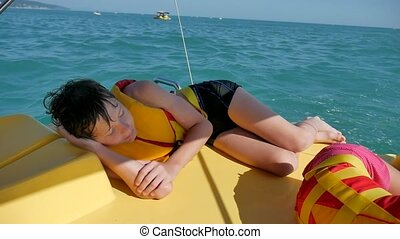 boy teenager sleeping on boat in the sea. boy teenager resting on a yacht boat catamaran on the water in the ocean